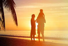 Romantic couple with little child at sunset beach Royalty Free Stock Photo