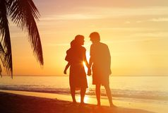 Romantic couple with little child at sunset beach Royalty Free Stock Image