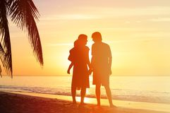 Romantic couple with little child at sunset beach Stock Images