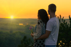 Romantic couple look on sun, evening on outdoor, beautiful landscape and bright yellow sky, love tenderness concept, young adult p Stock Photos