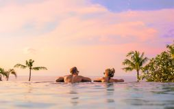 Romantic couple looking at beautiful sunset in luxury infinity pool. Romantic couple looking at beautiful sunset in luxury tropical infinity pool royalty free stock photos