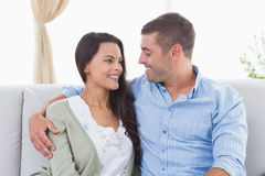 Romantic couple looking at each other on sofa Stock Photos