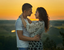 Romantic couple looking at each other at sunset on outdoor, beautiful landscape and bright yellow sky, love tenderness concept, yo Royalty Free Stock Images
