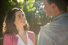 Romantic couple looking face to face in garden. On a sunny day Royalty Free Stock Image