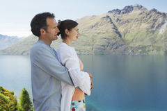Romantic Couple Looking At Mountain Lake Royalty Free Stock Images
