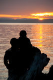 Romantic Couple Looking at Sunset Over Water Stock Photo