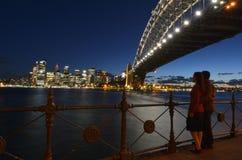 Romantic couple looks at Sydney skyline at dusk stock image