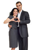 Romantic couple in love, dressed in black suit, show heart shape from hands, isolated white Stock Photos