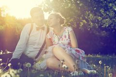 Romantic couple in love flirting on grass in sunny park. Vintage Royalty Free Stock Image