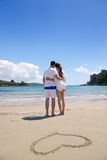 Romantic  couple in love  have fun on the beach with heart drawi Royalty Free Stock Photography