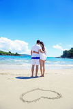 Romantic  couple in love  have fun on the beach with heart drawi Royalty Free Stock Image
