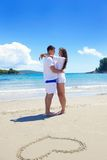 Romantic  couple in love  have fun on the beach with heart drawi Stock Image