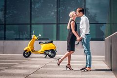 Romantic couple in love, hold hands and kiss standing under a skyscraper hot summer day royalty free stock photos