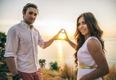 Romantic couple. Couple in love kissing at sunset - Lovers on a romantic date outdoors making a heart shape with hands Stock Photos