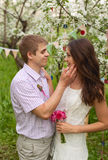 A romantic couple in love outdoors. Among the trees in blossommen tender palms face of his beloved woman Stock Photos