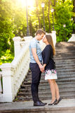 Romantic couple in love posing on stairs at park at sunny day Stock Image