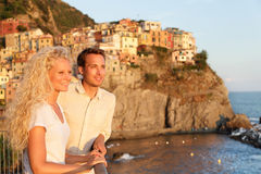 Romantic couple in love by sunset in Cinque Terre. Romantic couple in love by sunset on holidays travel. Young beautiful couple enjoying ocean view romance Royalty Free Stock Image