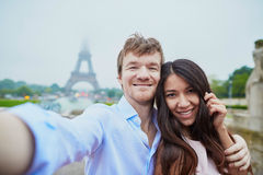 Romantic couple in love taking selfie near the Eiffel tower in Paris on a cloudy and foggy rainy day Royalty Free Stock Images