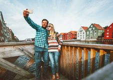 Romantic couple in love taking selfie by smartphone. Traveling together in Norway vacations weekend Lifestyle outdoor scandinavian houses Trondheim city Stock Image
