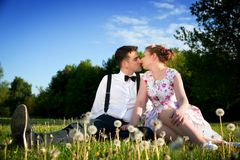 Romantic couple in love about to kiss sitting on grass. Romantic couple in love about to kiss while sitting on grass in spring park. Dating, women in dress and Royalty Free Stock Photos