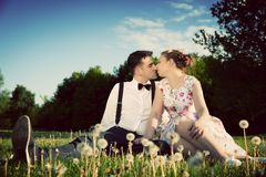 Romantic couple in love about to kiss sitting on grass. Vintage. Romantic couple in love about to kiss while sitting on grass in spring park. Vintage date, women Royalty Free Stock Image