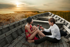 Romantic couple. In love with wineglasses of wine in old boat on sea shore at sunset Stock Photo