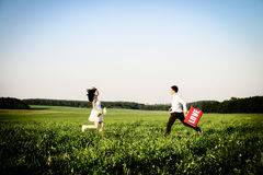 Romantic couple of lovers in field runs towards each other Royalty Free Stock Image