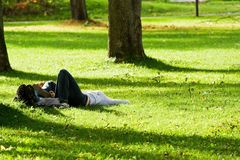 Romantic couple lying on the grass. Looking at the sky Stock Photography