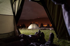 Romantic couple lying in tent with view of night camping. Romantic couple lying in tent with a view of night camping, mighty mountains and luminous town. Tourist Royalty Free Stock Photo