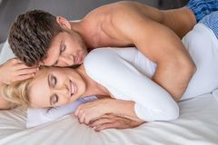 Romantic Couple Lying on White Bed Royalty Free Stock Photography
