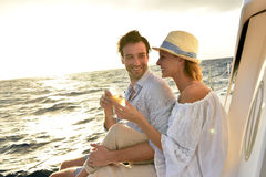 Romantic couple making toast at sunset sitting on sailing boat Royalty Free Stock Image