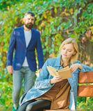 Romantic couple meet in park. woman read intersting book. relax on park bench. Literature. autumn or spring time. Romantic couple meet in park. women read royalty free stock photos