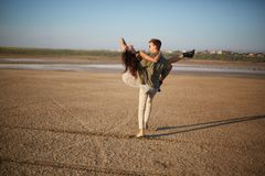 Romantic couple on a natural background. Boyfriend holding girlfriend in hands. Romance concept. Copy space. Stock Images