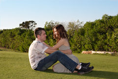 Romantic couple at nature. Romantic couple flirting at nature, siting in a park stock images