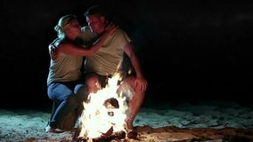 Romantic couple near fire at night while camping stock video