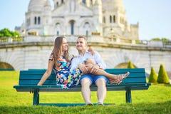Romantic couple near Sacre-Coeur cathedral on Montmartre, Paris. Romantic couple sitting together on bench near Sacre-Coeur cathedral on Montmartre, Paris Royalty Free Stock Images