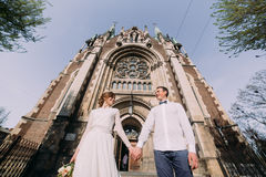 Romantic couple, newlywed valentynes posing holding hands near old gothic church Stock Photo