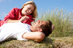 Romantic couple outdoors. Romentic couple outdoors laying in sand dunes royalty free stock photos