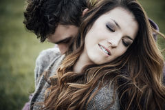 Romantic couple outdoors. They are sitting on grass and hugging, she is biting her lip Stock Photo