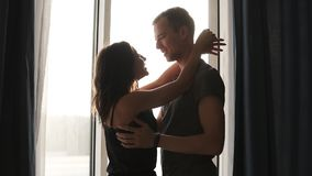 Romantic couple in pajamas. Happy time together. Hugs closeness love emotion kiss. Beautiful young adult caucasian woman. And man standing in front of the stock video footage