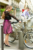 Romantic couple in Paris. Taking bikes for rent Royalty Free Stock Image