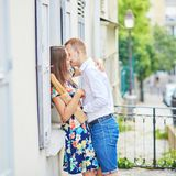 Romantic couple in Paris kissing each other on Montmartre. Romantic couple together in Paris kissing each other on Montmartre, girl is holding traditional French Stock Photography