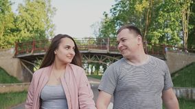 Romantic couple in the park in the summer. They go and joyfully look into each other`s eyes. In the background is a. Bridge. Happy together stock video footage