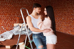 Romantic couple. Passion time. Young loving couple embracing and looking to each other at home. Royalty Free Stock Image