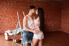 Romantic couple. Passion time. Young loving couple embracing and looking to each other at home. Royalty Free Stock Photo