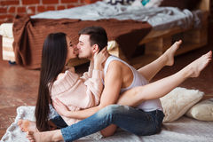 Romantic couple. Passion time. Young loving couple embracing and looking to each other at home. Stock Photography