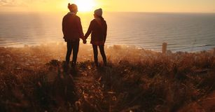 Romantic couple on peak at sunset. Silhouette of young men and women in love standing on the mountain peak holding hands and looking at each other with seascape stock photography