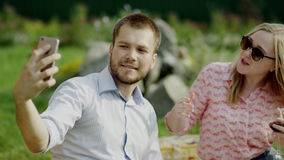 Romantic couple on a picnic. Romantic couple of man and woman taking selfie by the phone sitting on a grass on a picnic stock video footage