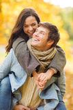 Romantic couple playing in the autumn park. Holidays, love, travel, tourism, relationship and dating concept - romantic couple playing in the autumn park Royalty Free Stock Photography