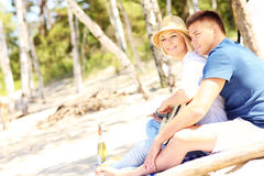 Romantic couple playing guitar at the beach Stock Photos
